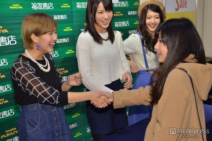 ファンと握手を交わす岡井千聖(左)