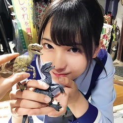 恐竜のフィギュアを持って笑顔を浮かべる小坂菜緒(撮影:齊藤京子)/提供写真