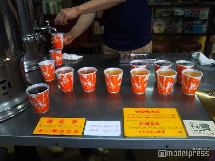 大きなタンクから温かい涼茶がカップに並々と注がれます。お店の人に10$を手渡して、好みの涼茶を受け取る/提供画像