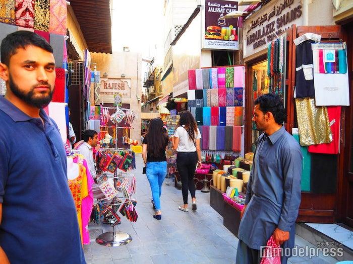 たくさんの店の前に商人が立っていて、客引きをしている(C)モデルプレス