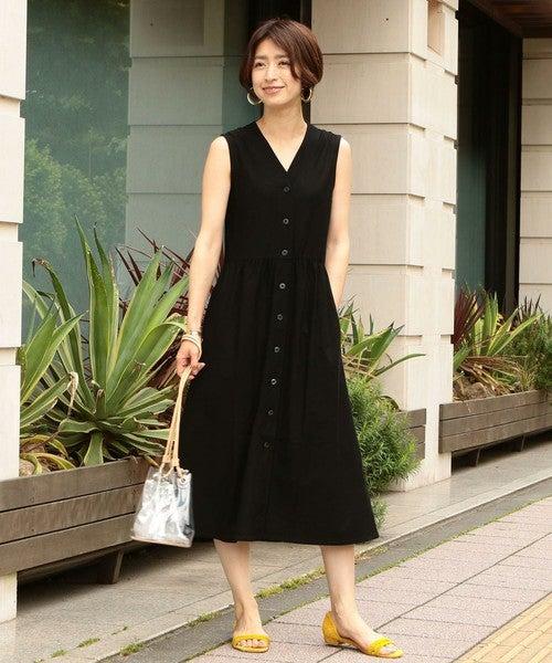黒のノースリーブの前ボタンワンピースを着た女性