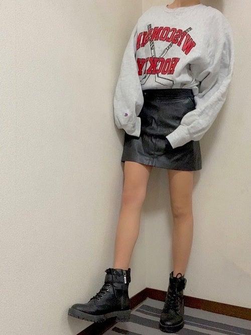 グレーベースのオーバーサイズのロゴプリントスエットに黒のレザーミニタイトスカートを合わせ、黒のアンクル丈シューズを履いたコーデ