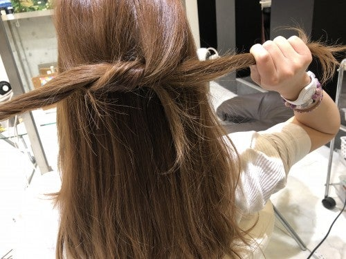 分けとったトップの髪をさらに2つに分けて髪同士をぎゅっと結びます。