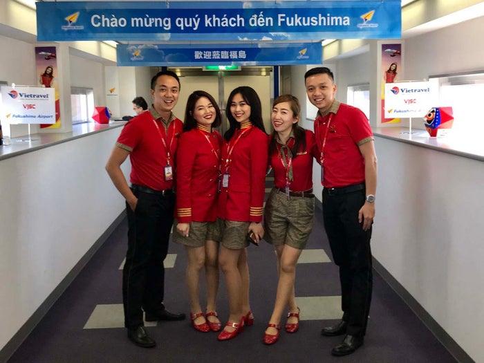 谷さん(左から2番目)と佐久間さん(左から4番目)。福島空港チャーター便の到着時撮影