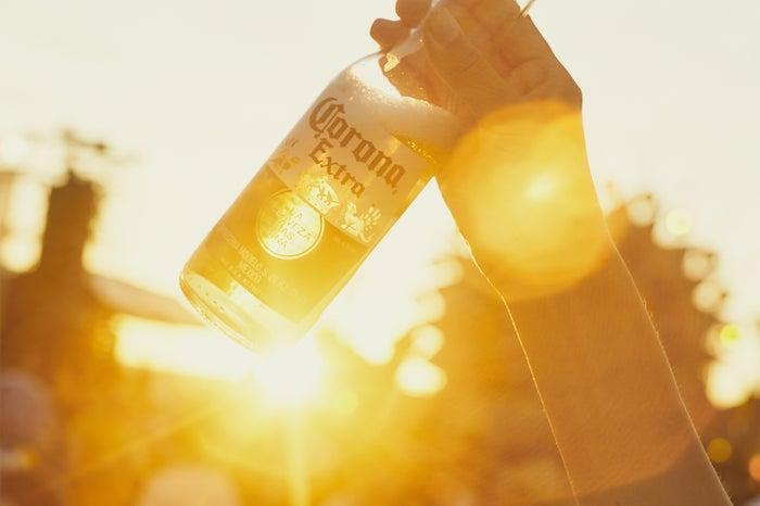 メキシコのプレミアムビール「コロナ・エキストラ」/飲み口に差し込まれたライムをギュッと絞ればより爽やかな味わいに(提供画像)