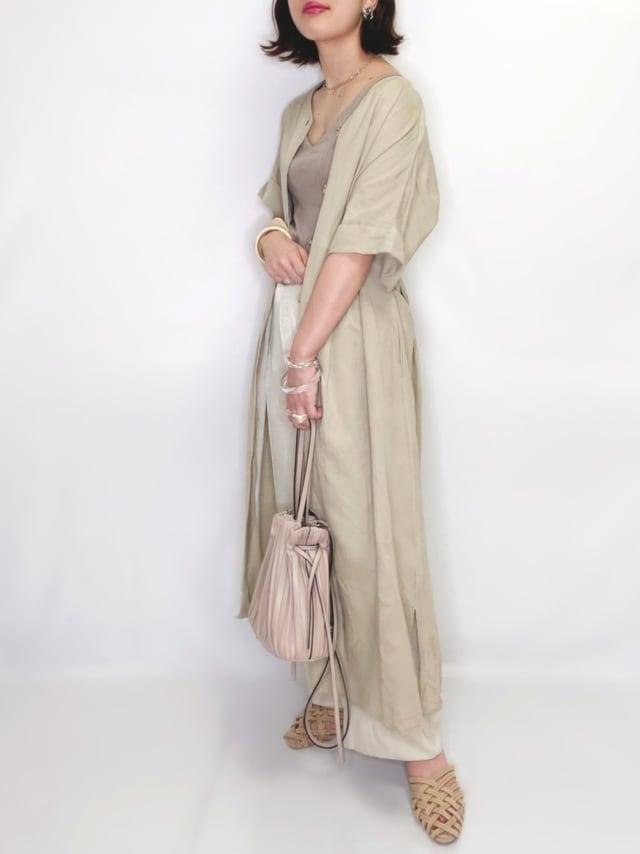 ベージュのワンピースにzaraのプリーツバッグを持った女性