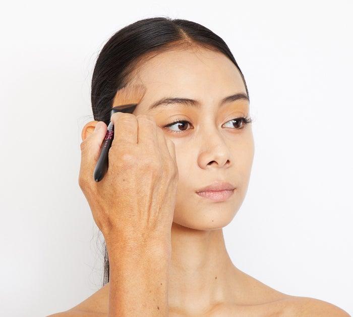 ブラシで頬骨にそってぼかしていく。この時、目尻・こめかみまで伸ばすのが引き締めのポイント。仕上げはベース同様、スポンジでなじませる。